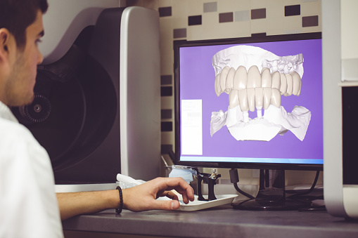 A hygienist looking at a digital impression of a patient's teeth at Mid Valley Dental in Menasha, WI
