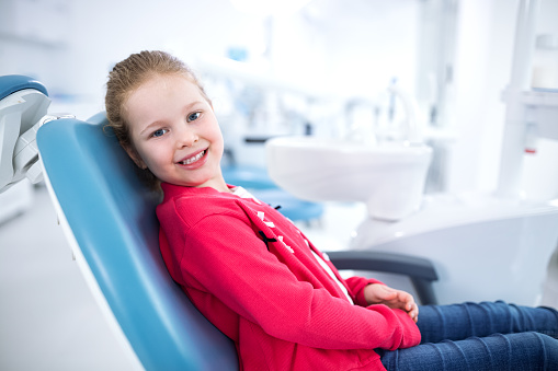 A girl in a dental chair smiling after receiving air abrasion during a dental cleaning at Mid Valley Dental in Menasha, WI